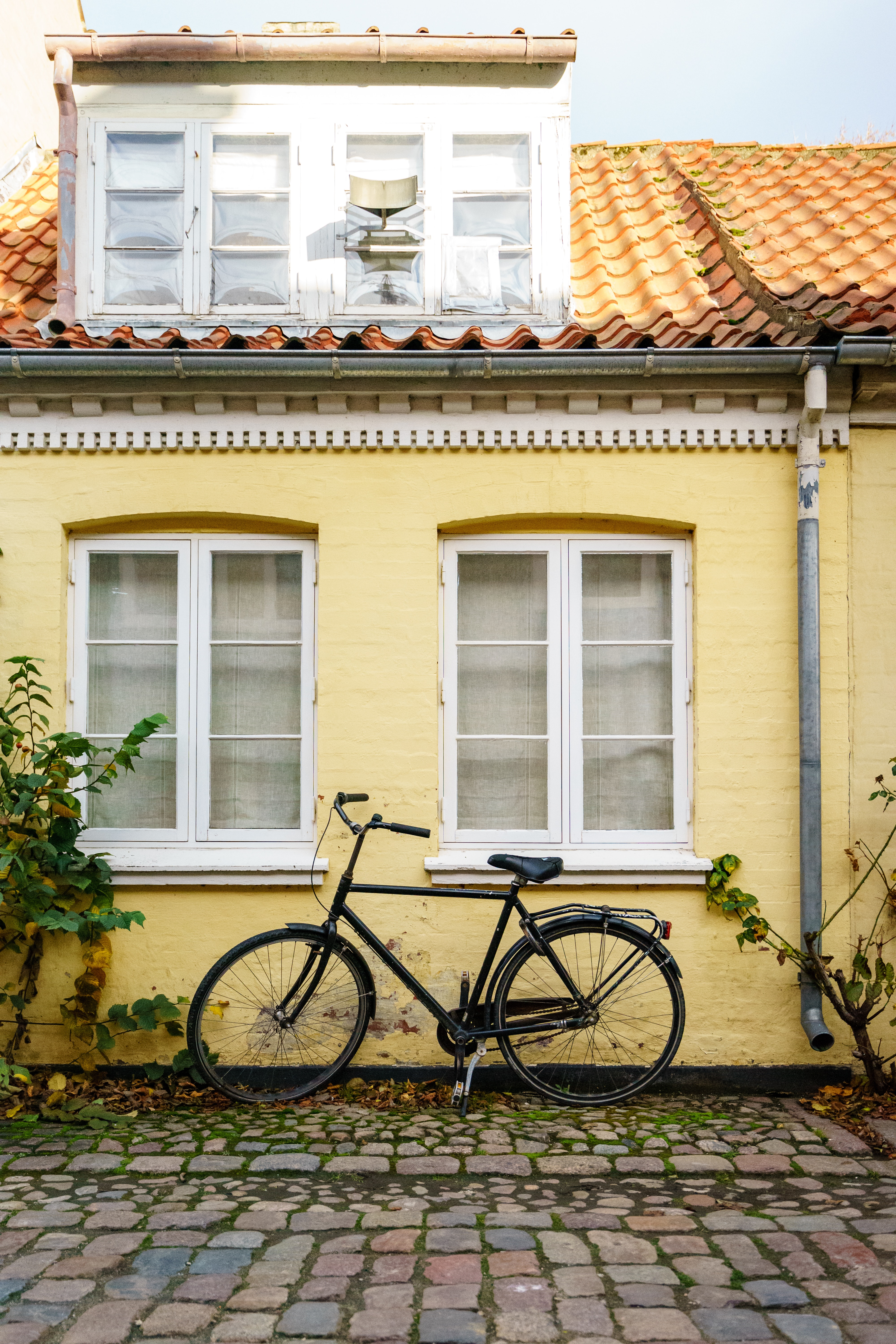 black bicycle parked beside yellow painted house